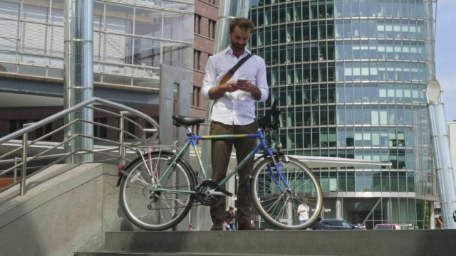 Slow motion video of businessman with his bicycle checking mobile phone