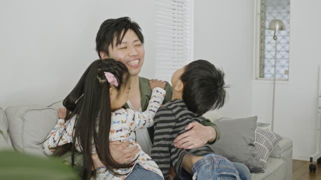 ソファの上で自宅で父親を抱きしめる子供たちのスローモーションビデオ - 兄弟点の映像素材/bロール