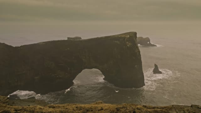 slow motion video of dyrholaey arch in a overcast day - dyrholaey stock videos & royalty-free footage