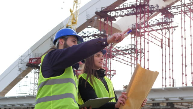 Slow Motion video of engineer and architect with blueprints on construction site