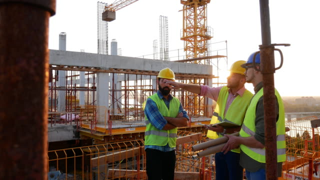 slow motion video of engineers working on the construction site - headwear stock videos & royalty-free footage