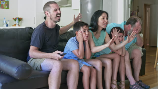 Slow motion video of family disappointed watching television