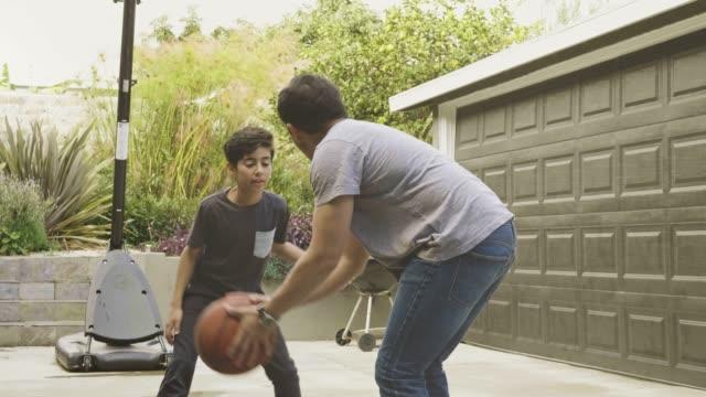 vídeos y material grabado en eventos de stock de slow motion video de padre e hijo jugando baloncesto en el hogar - familia con un hijo