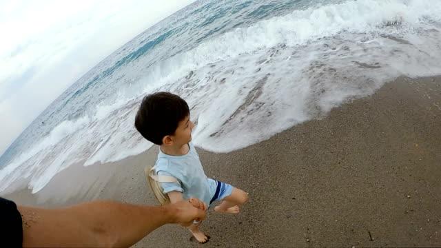 vídeos de stock e filmes b-roll de slow motion video of father and son running by the water - câmara vestível