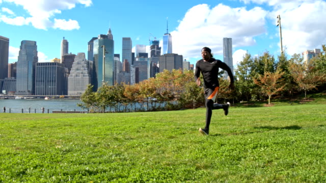 slow motion video of fit man jogging in park in new york - one man only stock videos & royalty-free footage