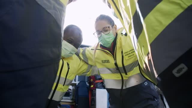 vídeos y material grabado en eventos de stock de vídeo a cámara lenta de cuatro paramédicos acurrucados juntos, mirando a la cámara - trabajador de primera línea