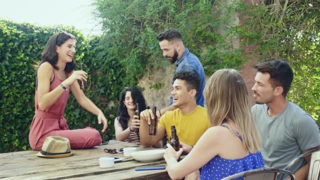 slow motion video von freunden, die sich im innenhof mit bier sozialisieren - nah stock-videos und b-roll-filmmaterial