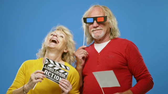slow motion video of fun senior couple holding movie props - 3d glasses stock videos & royalty-free footage