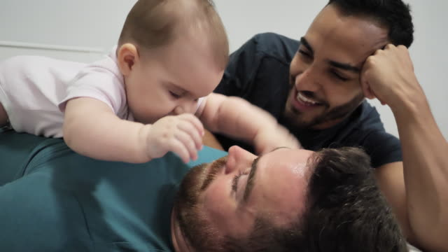slow motion video of gay couple in bedroom with adopted baby - parent stock videos & royalty-free footage
