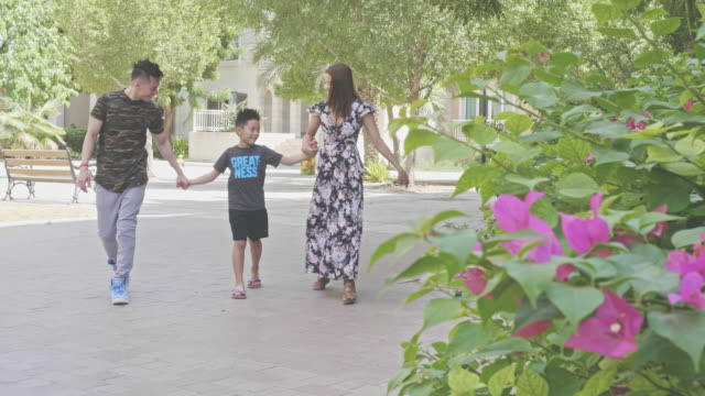 Slow motion video of happy Filipino family walking outdoors holding hands