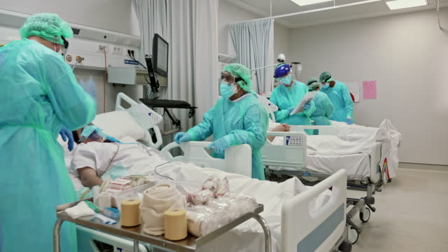 vídeos de stock e filmes b-roll de slow motion video of healthcare teamwork taking care of patients in icu - epidemia