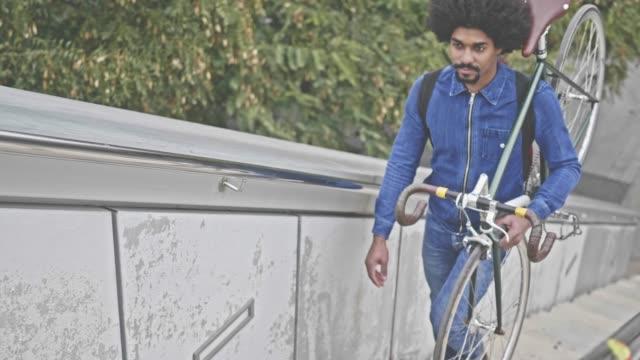 Slow motion video van hipster dragen van zijn fiets in een park trap