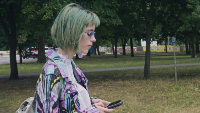 vídeos de stock e filmes b-roll de slow motion video of hipster girl walking in the street with mobile phone - punk