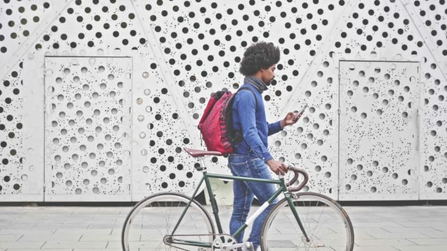 vídeos de stock e filmes b-roll de slow motion video of hipster with bicycle walking in the street with mobile phone - funky
