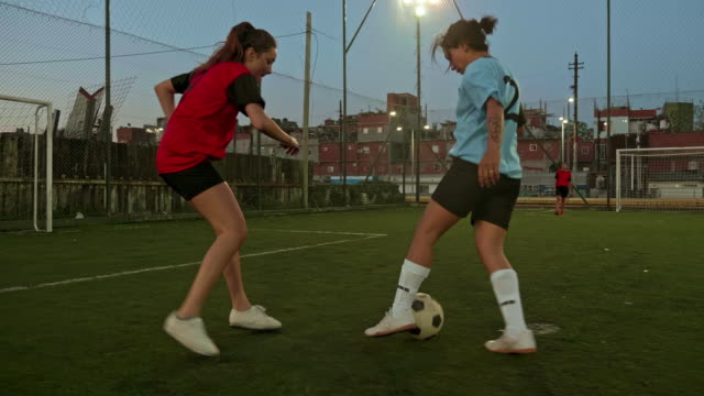 slow motion video of hispanic female footballers playing football at dusk - argentinian culture stock videos & royalty-free footage