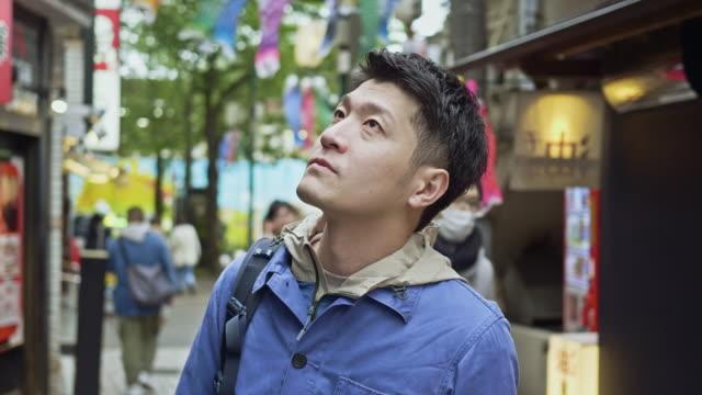 vídeos de stock e filmes b-roll de slow motion video of japanese handsome man looking around in the street at tokyo - encontrar