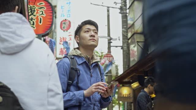 stockvideo's en b-roll-footage met slow motion video van de japanse man te kijken naar mobiele telefoon voor begeleiding in tokio - begeleiding