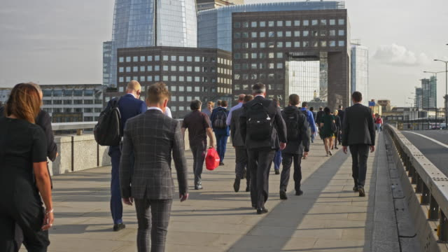 slow motion video of large group of businesspeople walking in london financial district - rear view stock videos & royalty-free footage