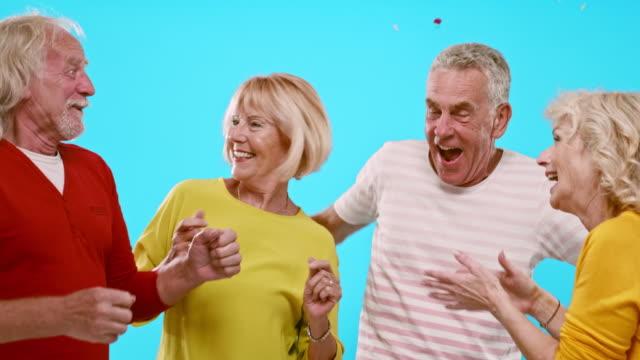 vídeos de stock, filmes e b-roll de vídeo em câmera lenta de idosos rindo dançando e celebrando um ano novo - fundo colorido