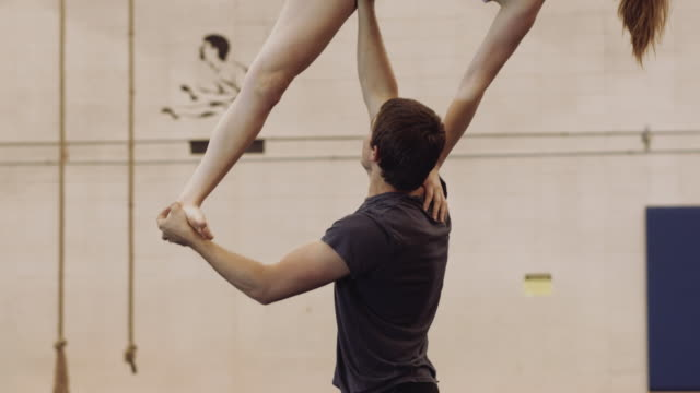 Slow motion video of male gymnast holding woman with one arm