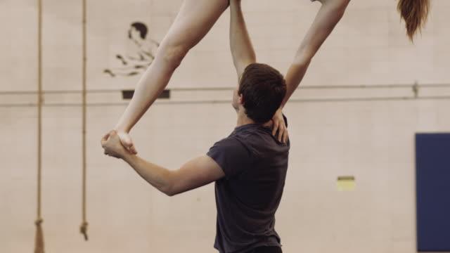 vidéos et rushes de ralenti vidéo de femme holding gymnaste avec un bras - s'impliquer à fond