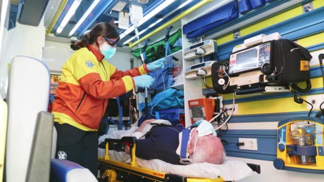vídeos y material grabado en eventos de stock de video a cámara lenta de la mujer madura paramédico que se preocupa por el hombre mayor en stretcher - ambulancia