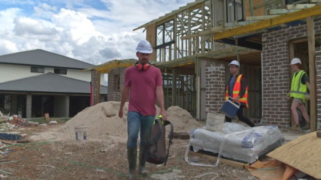 slow motion video of multi-ethnic construction team leaving the construction site - construction worker stock videos & royalty-free footage