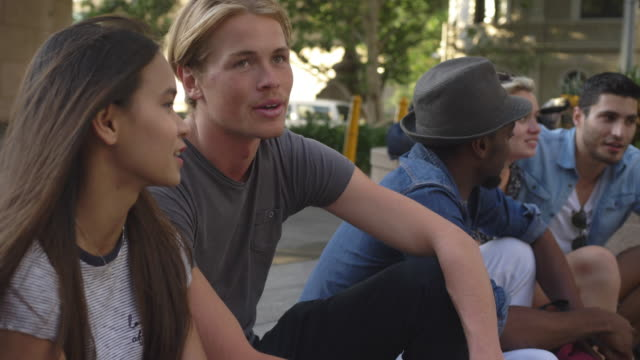 Slow motion video of multi-ethnic friends talking while sitting in city