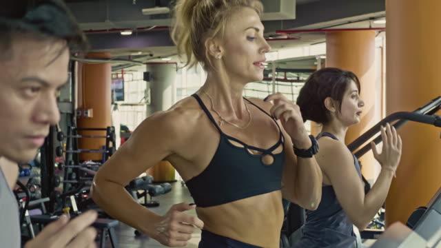 stockvideo's en b-roll-footage met slow-motion video van multi-etnische groep van atleten joggen op een loopband in de sportschool - loopband fitnessapparaat