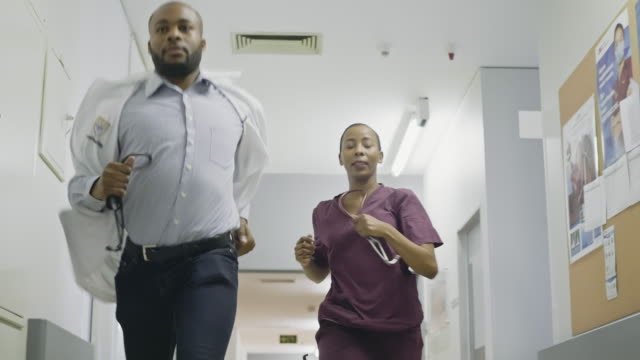 Slow motion video of nurse and doctor running down hospital corridor