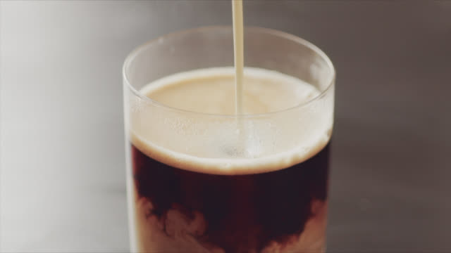 4k slow motion video of pouring milk in coffee - coffee cup stock videos & royalty-free footage