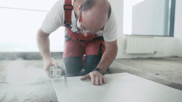 stockvideo's en b-roll-footage met slow-motion video van professionele tegelzetter snijden tegel - installeren