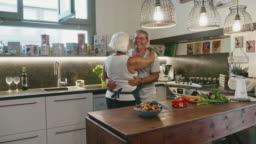 Slow Motion Video of Senior Couple Dancing while Preparing Lunch in Family Kitchen