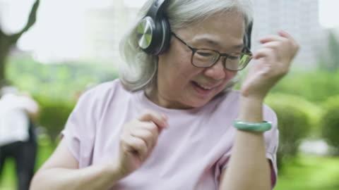 slow motion video av senior kvinna lyssnar på musik och dans - aktiva pensionärer bildbanksvideor och videomaterial från bakom kulisserna