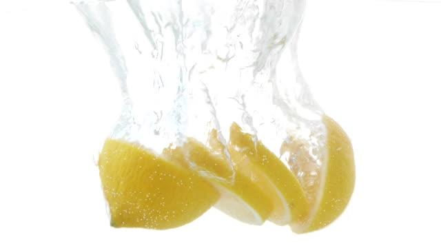 スライスされたレモンが水に落ちるスローモーションビデオ - 酸点の映像素材/bロール