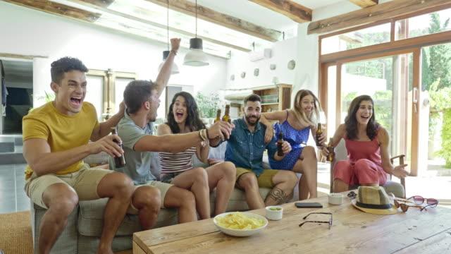 stockvideo's en b-roll-footage met slow motion video van sportliefhebbers tv kijken en het juichen van hun team - beer alcohol