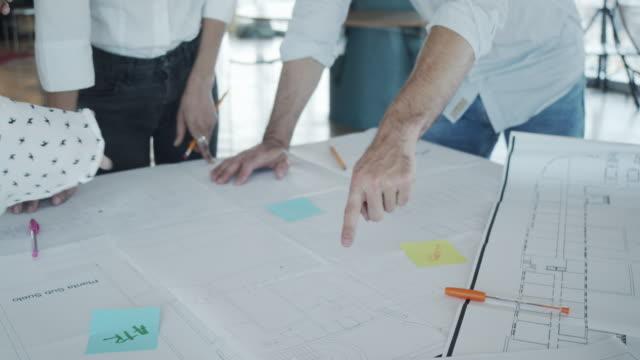 vídeos y material grabado en eventos de stock de vídeo a cámara lenta de tres arquitectos/diseñadores que trabajan juntos en su nuevo proyecto - cianotipo plano