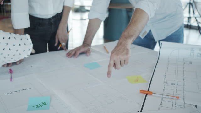 vídeos de stock e filmes b-roll de slow motion video of three architects/designers working together on their new project - plano descrição física