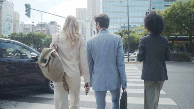 slow motion video of three business people crossing the street in the city - avenida 9 de julio stock videos & royalty-free footage