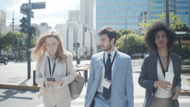 vídeos de stock e filmes b-roll de slow motion video of three business people crossing the street in the city - avenida 9 de julio