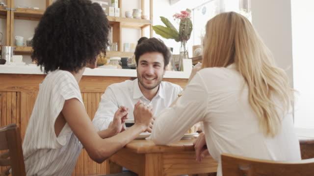 vidéos et rushes de vidéo de mouvement lent de trois personnes d'affaires ayant une réunion ensemble au café - pause déjeuner
