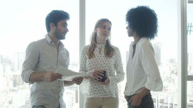vídeos de stock, filmes e b-roll de vídeo em câmera lenta de três empresários em um escritório moderno conversando juntos. eles estão de pé contra as janelas grandes. - afro