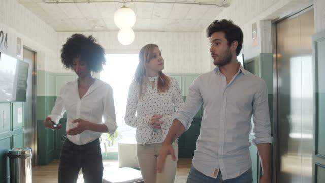 vídeos de stock, filmes e b-roll de vídeo em câmera lenta de três empresários em um escritório moderno conversando e andando juntos. eles estão em um espaço de coworking compartilhado contemporâneo. - estilo de cabelo