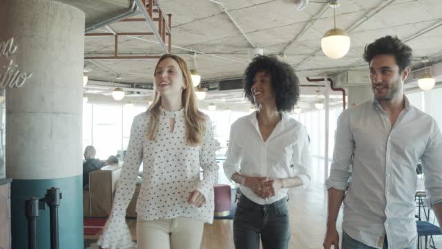 vidéos et rushes de vidéo au ralenti de trois gens d'affaires dans un bureau moderne parlant et marchant ensemble. ils sont dans un espace de coworking contemporain partagé. - trentenaire