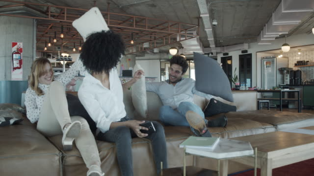 slow motion video of three  colleagues pillow fighting together at the office during a break - pillow fight stock videos & royalty-free footage