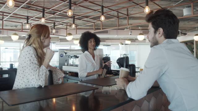 vídeos y material grabado en eventos de stock de vídeo a cámara lenta de tres colegas tomando un descanso de café en su moderno espacio de coworking - estudio lugar de trabajo