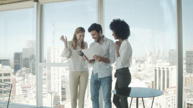 vídeos de stock, filmes e b-roll de vídeo em câmera lenta de três colegas trabalhando juntos em seu escritório moderno - estilo de cabelo