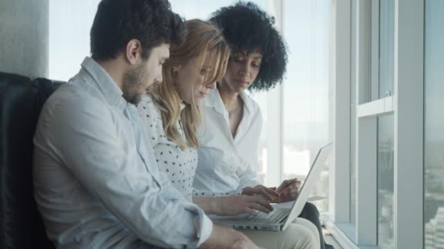 vídeos de stock e filmes b-roll de slow motion video of three colleagues working together with a laptop - arranha céu