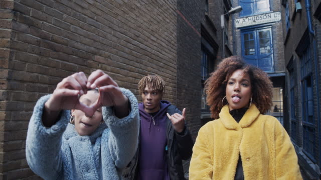 Slow motion video of three hip friends dancing together outdoor in the city