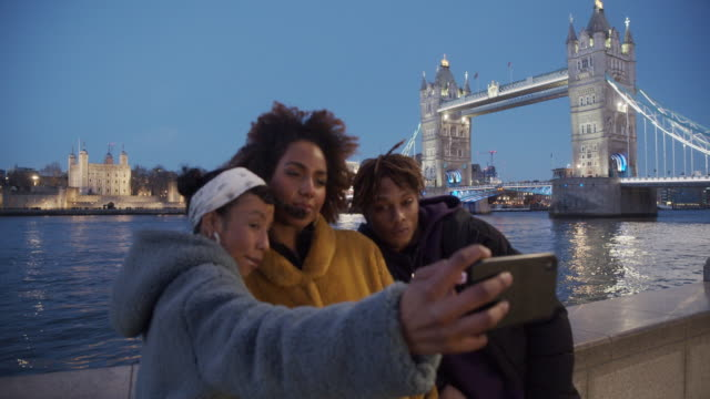 slow motion video of three young adult hip friends taking a selfie in london near tower bridge - focus on background, on the tower bridge - focus on background stock videos & royalty-free footage